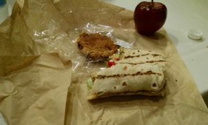 Picture of a vegan wrap, a red aple and a half eaten cookie